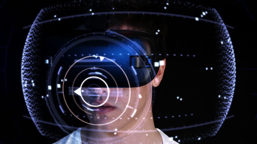 Close-up shot of a young man wearing VR Headset playing virtual reality games. Futuristic hud around him.