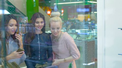 Ladies standing by the shopping window in the mall, emotionally discuss shopping.