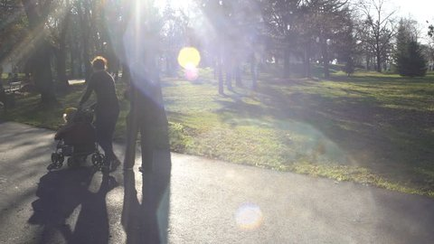 NIS, SERBIA, NOVEMBER 2016: Silhouettes of people walking in a park on a sunny autumn day. Deliberate lens flares contribute to the pleasant dreamy atmosphere.