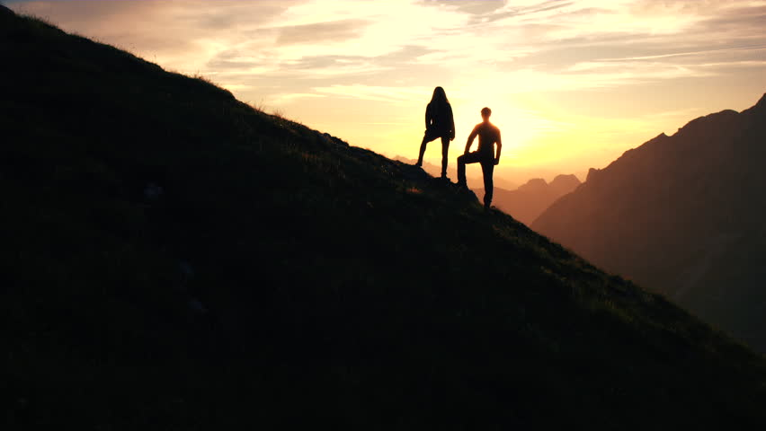 Aerial, edited - Silhouette of a couple giving each other a high five celebrating successful climb on the mountain in beautiful sunset | Shutterstock HD Video #22952896