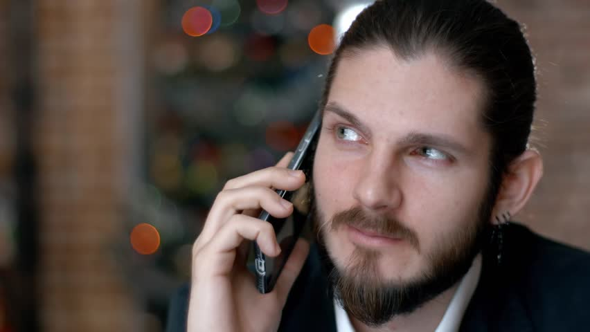 Handsome bearded businessman talking on the phone cheerfully during his coffee break on the cafe terrace | Shutterstock HD Video #22958926