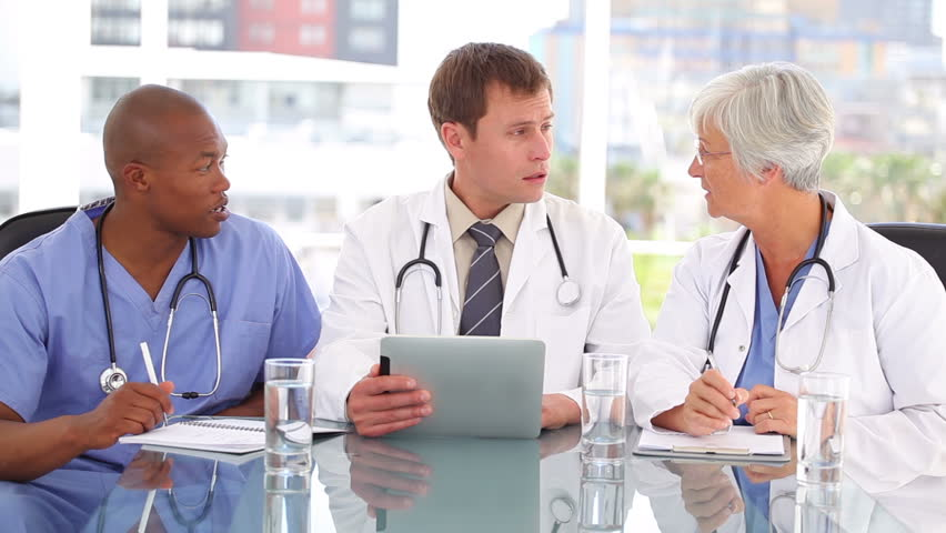 Serious doctor talking with his colleagues about a tablet pc in a bright room