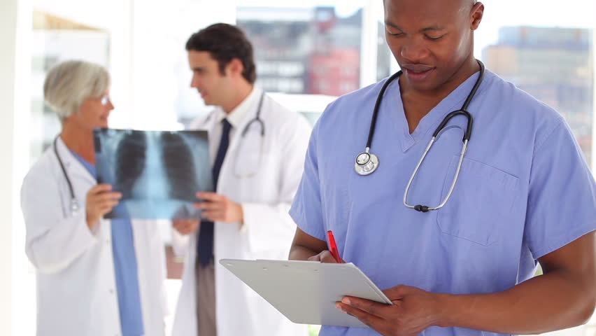 Nurse writing on a clipboard in front of doctors in a medical office