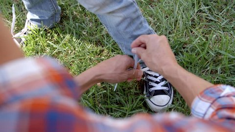 Father tying his son's shoelace in a park