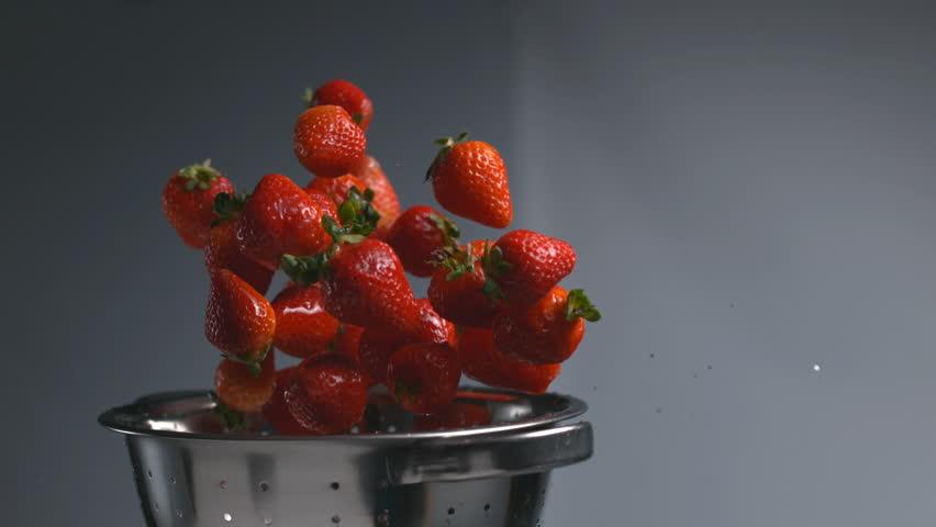Strawberries flying out of colander in super slow motion, shot on Phantom Flex 4K