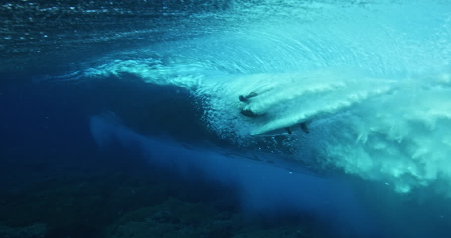 Underwater view of surfer riding ocean wave. Surfing shot from behind the wave.