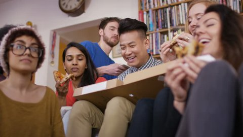 4K Large group of happy young friends eating takeaway pizza at home Dec 2016-UK