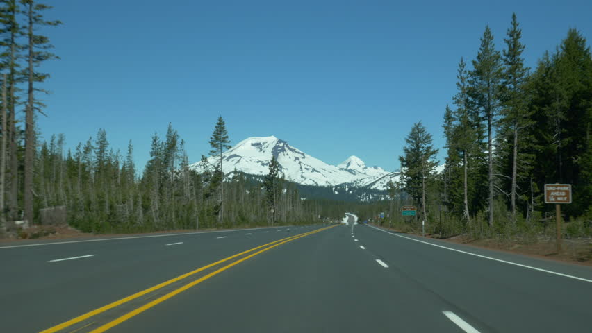 Traveling POV on the Cascade Lakes Scenic Byway, approaching Three Sisters and Broken Top, near Bend, Oregon.