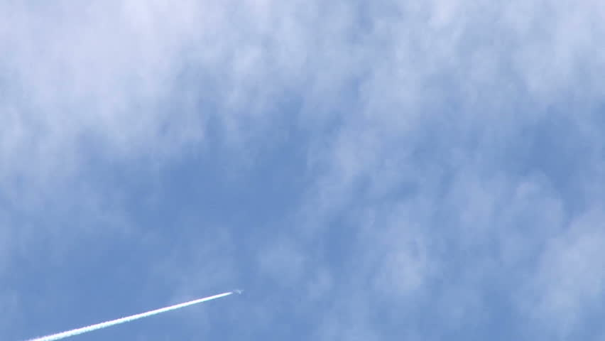 Airplane flies overhead on mostly sunny day leaving jet contrails behind.