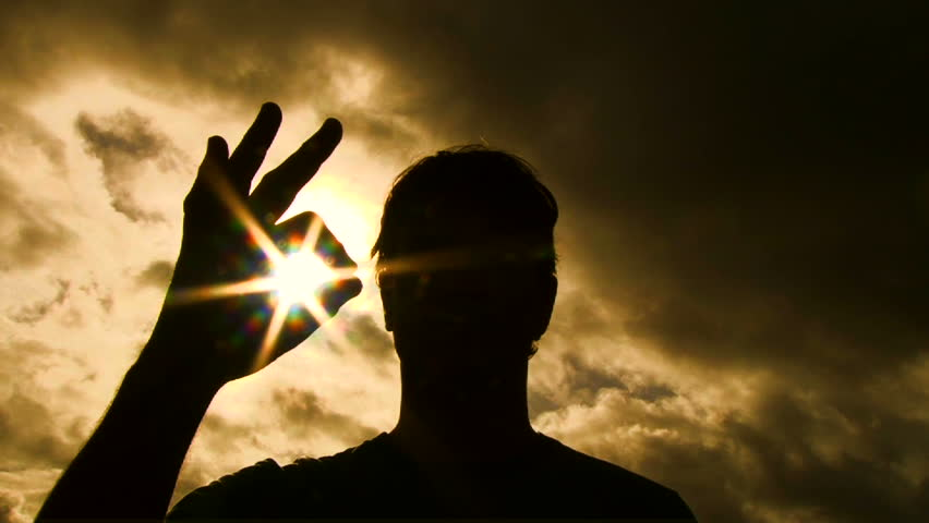 Person silhouetted raises hand into frame to give an a-okay sign with sun shining through to camera lens.