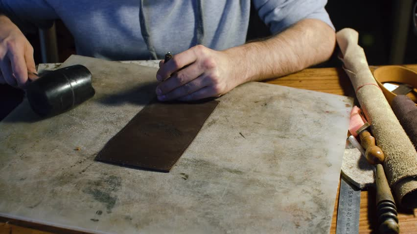A professional re-enactment craftsman making leather item