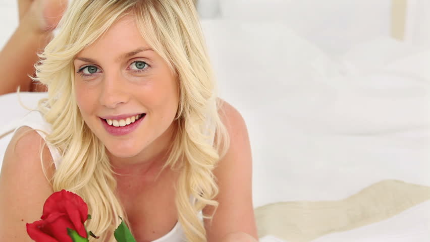 Blonde haired woman smelling a rose on her bed