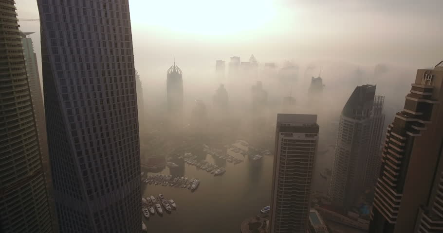 DUBAI, UAE - JANUARY 2, 2017: Aerial view of skyscrapers in Dubai Marina, at foggy sunrise. Dubai Marina is an artificial canal city, built along a two-mile (3 km) stretch of Persian Gulf shoreline