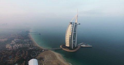 DUBAI, UAE - JANUARY 4, 2017:Aerial view of Burj al Arab hotel at sunrise.The Burj al-Arab is a symbol of Dubai and a luxury hotel standing on an artificial island next to Jumeirah beach.foggy weather