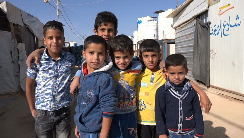 ZAATARI REFUGEE CAMP, JORDAN - NOVEMBER 2016: Syrian refugee kids pose for the camera inside the Zaatari camp in Jordan