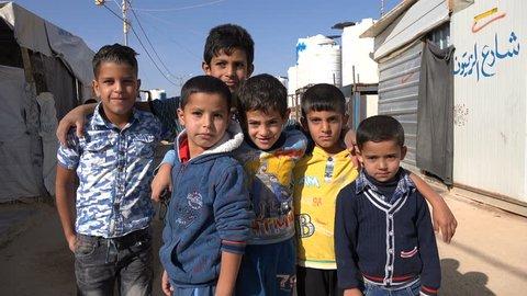 ZAATARI REFUGEE CAMP, JORDAN - NOVEMBER 2016: Syrian refugee kids pose for the camera inside the Zaatari camp in Jordan