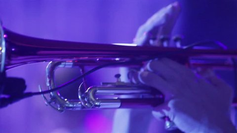 Man playing trumpet blue light neon close up. Performing wind instrument at stage in night club at new years party holding trumpet with finders and blowing – woman singing background shallow dof