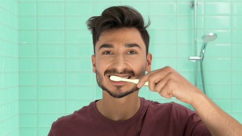 Man brushing teeth in bathroom portrait