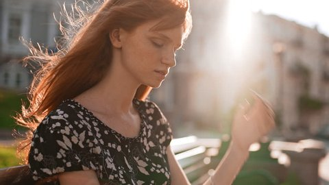 Beautiful redhead teen girl thoughtfully adjusts hair and looking away with pen in hand in slowmotion