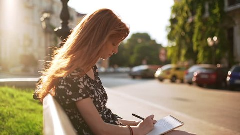 Foxy dreamy young girl sitting writing notes with sunlight on hair in slowmotion