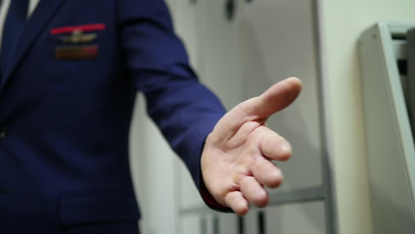 Slow-motion close-up shot of a male flight attendant's hand signaling a passenger in. (Santiago, Chile - Jun 2016)