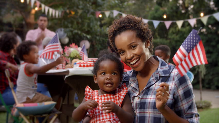 Black mother and baby girl wave flag at 4th July party