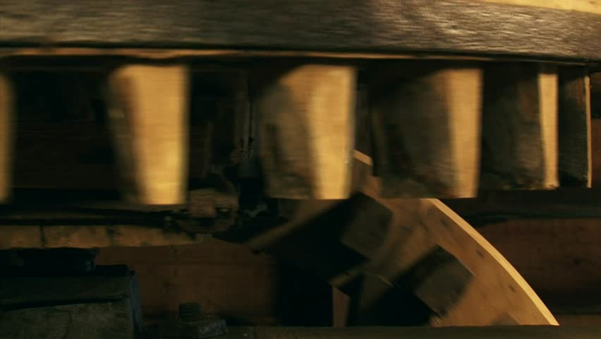 Cogwheels rotate in a 90-degree angle in an industrial corn mill - close up. Sound of creaking and groaning of the timber