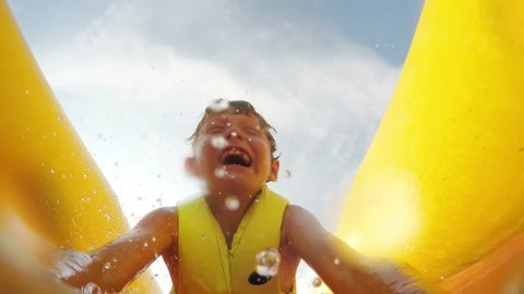 4K Video: Little boy slides fast by the inflatable slide into the water pool with active camera in front of his face