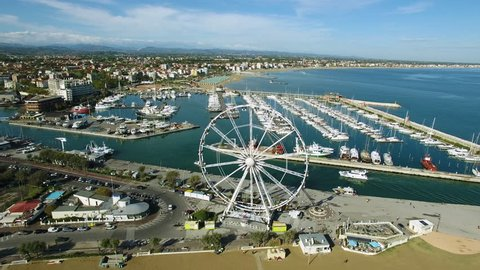 A beautiful Bay to Rimini with a floating yacht and Ferris wheel, aerial view