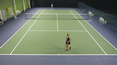Two women tennis players in black and white dress professionally trained on the tennis court. Fifty FPS