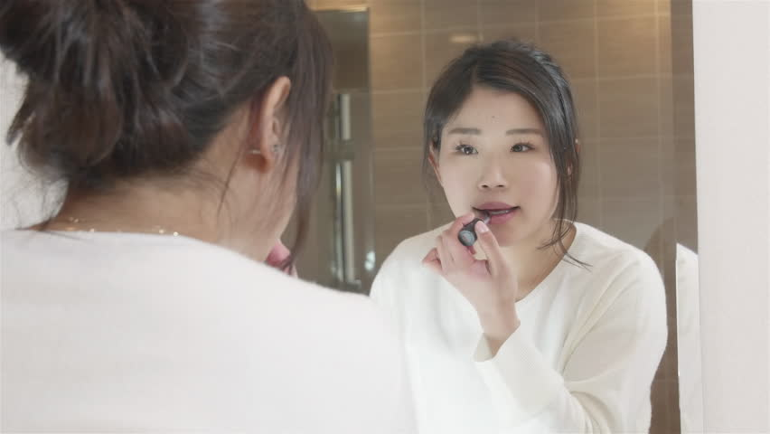 Young Japanese women putting on Lip stick in the mirror.