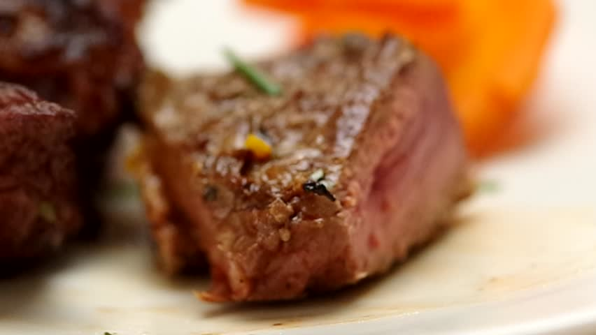 Knife cutting through delicious steak on white plate, blurry vegetable background