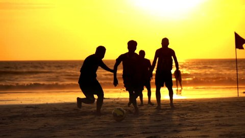 21.07.2016 Seminyak,Bali,Indonesia: Group of teenagers playing football on beach during sunset, super slow motion