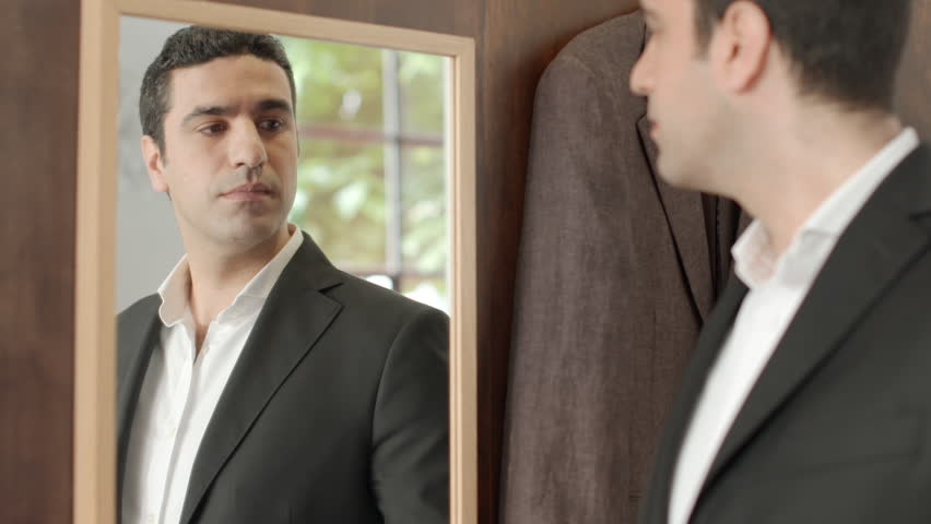 Male customer speaking to sales manager in fashion store for Looking mirror