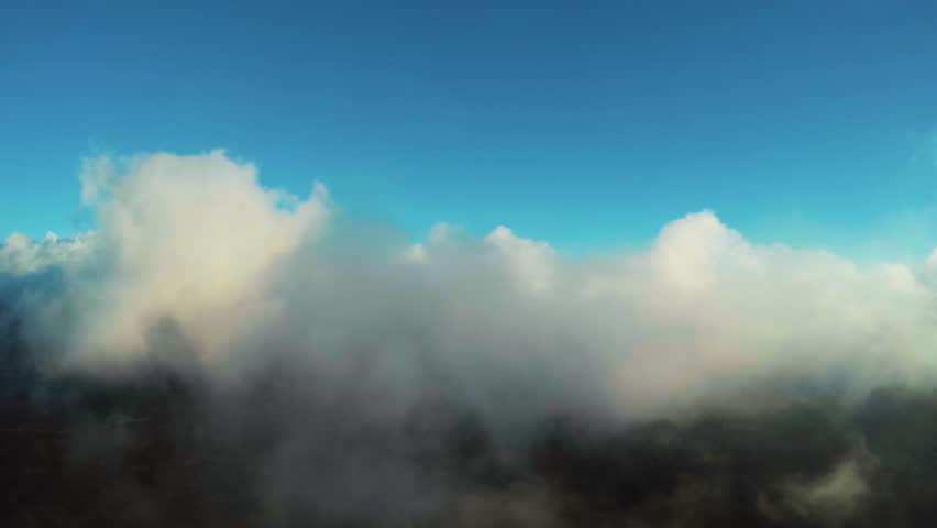 Aerial high above flying drone through misty foggy mountain landscape through low hanging clouds flight towards mountains and towards sun in far background beautiful day and blue sky white clouds 4k | Shutterstock HD Video #23315497
