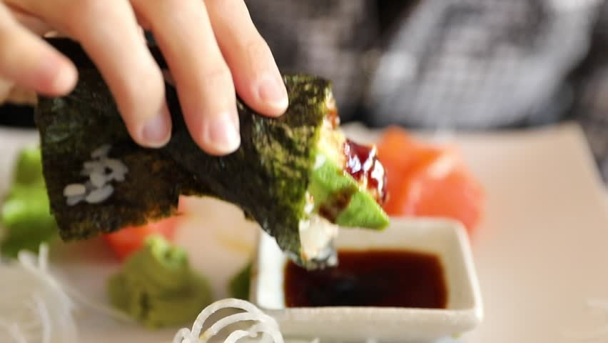 Slow motion focus on hand eating a California Temaki cone with shrimp tempura, rice, avocado and seaweed, in soy sauce bowl. Japanese fusion food, Asian cultures. Healthy food, light diet concept.