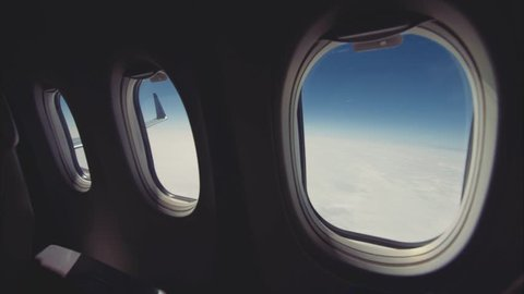 In-Flight shot. Slide camera, clouds and sky as seen through windows of an aircraft.