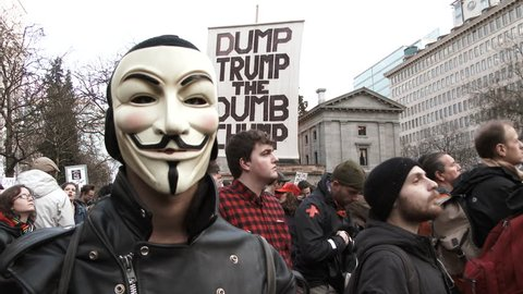 PORTLAND, OREGON - CIRCA 2017: Anonymous masked man looking at camera during an anti Donald Trump rally on inauguration day in Portland, Oregon.