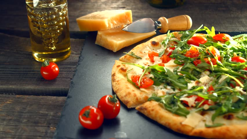Pizza Caprese with arugula, cheese, yoghurt and cherry tomatoes close up. Homemade delicious vegetarian pizza on wooden table. Dolly shot UHD 4K video footage.Ultra high definition 3840X2160