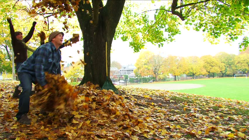 Friends enjoy a fall day by playing in leaf pile as man throws large amounts of leaves into the air and girls join in, slow motion.
