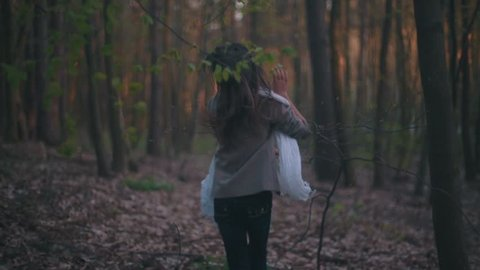 Little lost girl with a bright scarf running through the dark forest, she is frightened and lonely, she falls down, gets up and continues running. Forest mysteries, danger. Dark deserted wood.