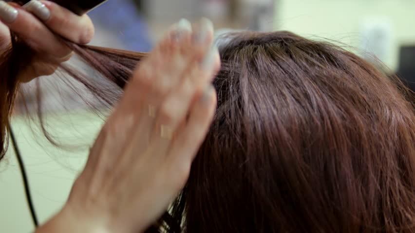 Hairdresser using straightener on beautiful woman hair in hair salon | Shutterstock HD Video #23387716
