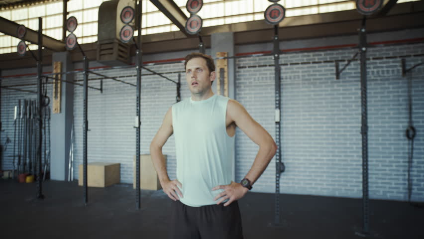 Man breathing deeply after intense gym session tired and out of breath