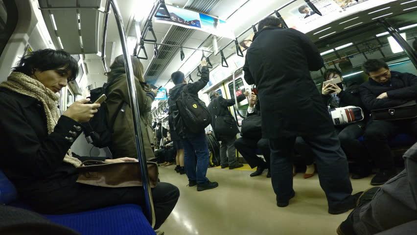 TOKYO, JAPAN - NOVEMBER 2016: People Riding Train, Drunk Guy Tries to Keep is Balance Near Door #23412766