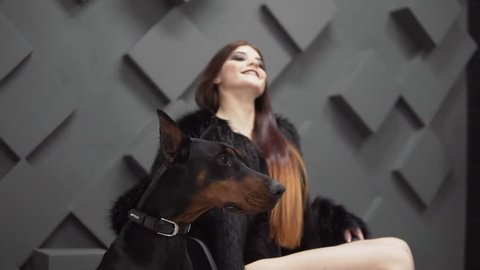 Sexy girl with long hair in black fur coat sitting near dog in studio