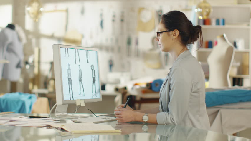 Beautiful Fashion Designer Sits At Her Desk Before Personal Computer, Using  Digital Drawing Tablet.