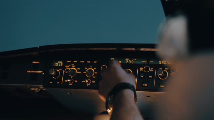 Close shot of glareshield - front panel of modern aircraft with co-pilot's hand turning knob on flight deck with lights. Interior