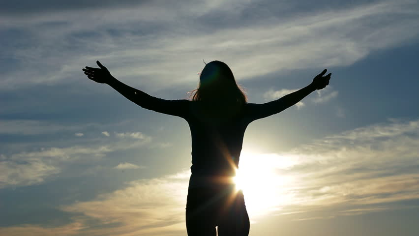 Silhouette young woman raising arms to sky
