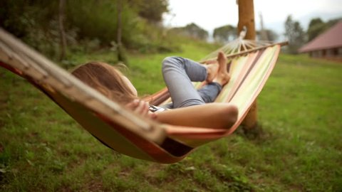 Young Caucasian female resting lying on hammock among two poles outdoors in slowmotion
