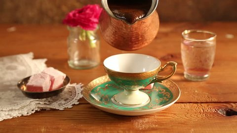 Pouring hot Turkish coffee in a traditional cup on a wooden table